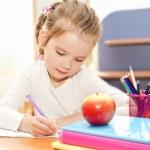 Little girl is writing at the desk  in preschool — Stock fotografie #44127777