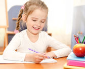 Cute little girl is writing at the desk  in preschool — Stock Photo