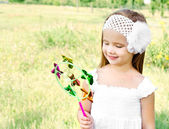 Smiling little girl playing with windmill toy — Stock Photo