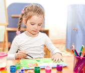 Little girl drawing with paint and paintbrush  — Stock Photo