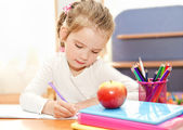 Little girl is writing at the desk  in preschool — Stockfoto