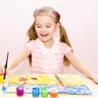 Cute smiling little girl drawing with paint and paintbrush  — Stock Photo #44671239