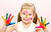 Cute smiling little girl with hands in paint — Foto de Stock
