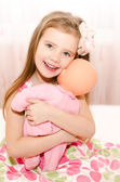 Adorable smiling little girl playing with a doll — Stock Photo