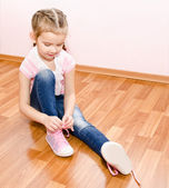 Cute little girl tying her shoes — Stock Photo