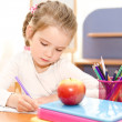 Cute smiling little girl is writing at the desk   — Stock fotografie #46321915
