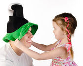 Little girl puts on the funny cap to her father isolated — Stock Photo