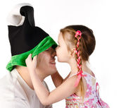 Little girl kissing her father in funny cap isolated  — Stok fotoğraf