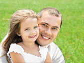 Outdoor portrait of happy smiling young man and little girl — Stock Photo