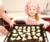 Smiling little girl in chef hat with baking sheet of cookies  — Stock Photo