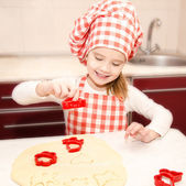 Little girl cuts dough with form for cookies  — Stock Photo