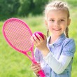 Adorable smiling little girl with racket and ball — Stock Photo