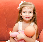 Adorable little girl playing with a doll — Foto Stock