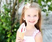 очаровательны улыбается маленькая девочка ест мороженое — Стоковое фото