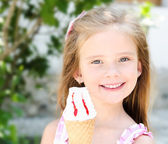 Adorable smiling little girl eating ice cream  — Stock Photo