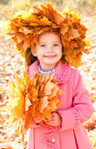 Autumn portrait of smiling little girl in maple wreath — Stock Photo