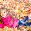 Autumn portrait of cute smiling little girl lying in maple leave — Stock Photo #49211345