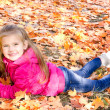 Autumn portrait of cute smiling little girl lying in maple leave — Stock Photo