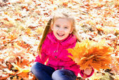 Autumn portrait of cute happy little girl with maple leaves — Stock Photo