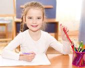 мило улыбается девочка пишет в стол — Стоковое фото