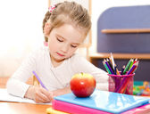 Cute smiling little girl is writing at the desk — Stock Photo