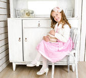 Adorable little girl sitting on chair with gift box — Stock Photo