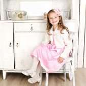 Adorable little girl sitting on chair  — Stock Photo