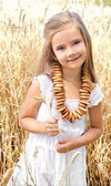 Smiling little girl on field of wheat with bagels  — Stock Photo