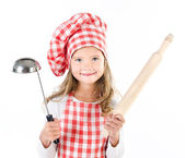 Smiling cute little girl in chef hat with ladle and  rolling pin — Stock Photo