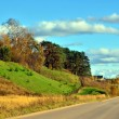Long road along the hills - autumn landscape. — Stock Photo