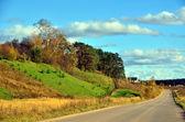 Largo camino a lo largo de las colinas - paisaje de otoño. — Foto de Stock