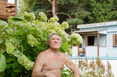 The elderly man has a rest in a garden — Stockfoto