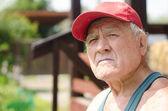 An elderly man in a red baseball cap — Stock Photo