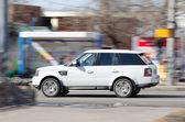 Bílé auto jeep vysokou rychlostí jde po ulici — Stock fotografie