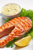 Grilled salmon steak with sauce, parsley and lemon — Stock Photo