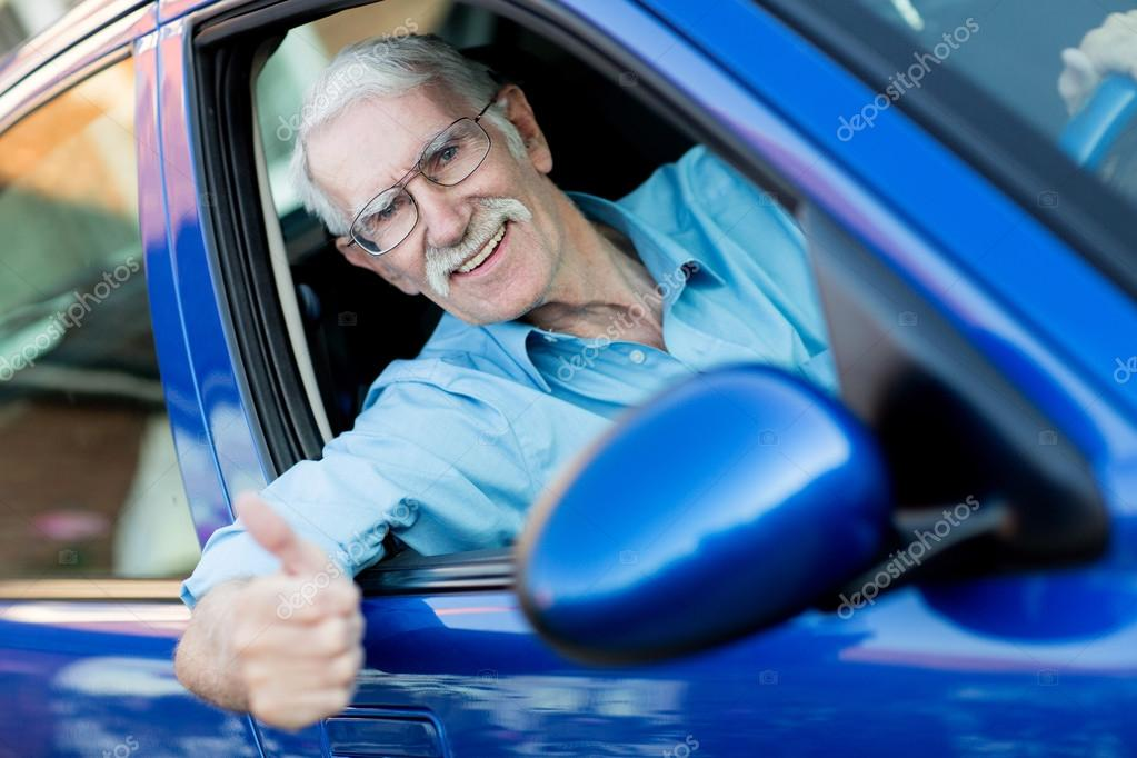 Happy male driver with thumbs up in a car  — Stock fotografie #12759434