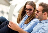 Couple on holidays with a laptop — Stock Photo