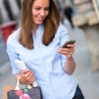 Shopping woman sending a text — Stock Photo #12807917