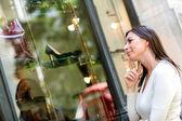 Thoughtful woman window shopping — Stock Photo