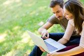 пара с помощью ноутбука на открытом воздухе — Стоковое фото