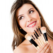 Woman holding make up brushes — Stockfoto
