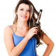 Beautiful woman curling her hair — Stock Photo