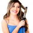 Stock Photo: Womstyling her hair with curler