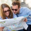 Stock Photo: Tourists looking at map