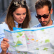 Stock Photo: Tourists looking at a map