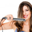 Woman using a hair straightener - Stock Photo