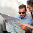 Travelers looking at a map — Stock Photo
