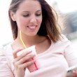 Woman enjoying a milkshake - Stockfoto