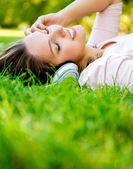 Kobieta ze słuchawkami w parku — Zdjęcie stockowe