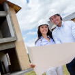 Stock Photo: Couple holding blueprints